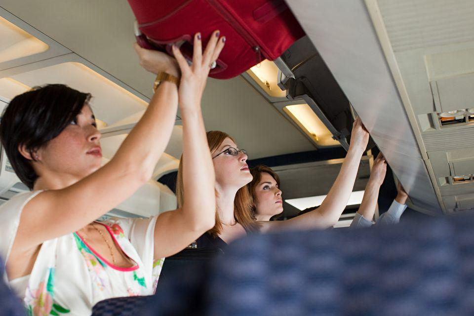 Passengers placing bags in overhead bins