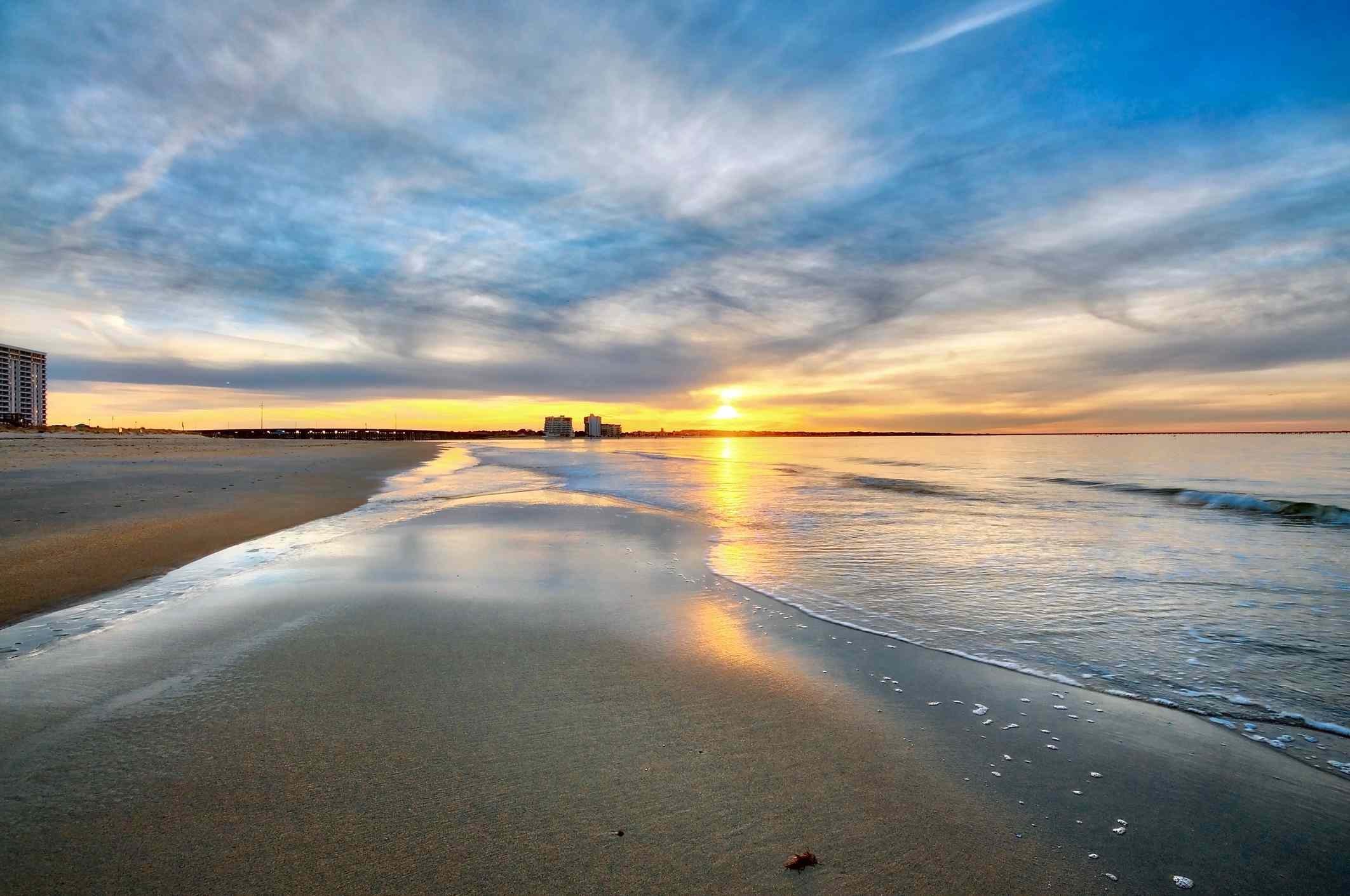 A colorful sunset on a calm tranquil sandy beach.