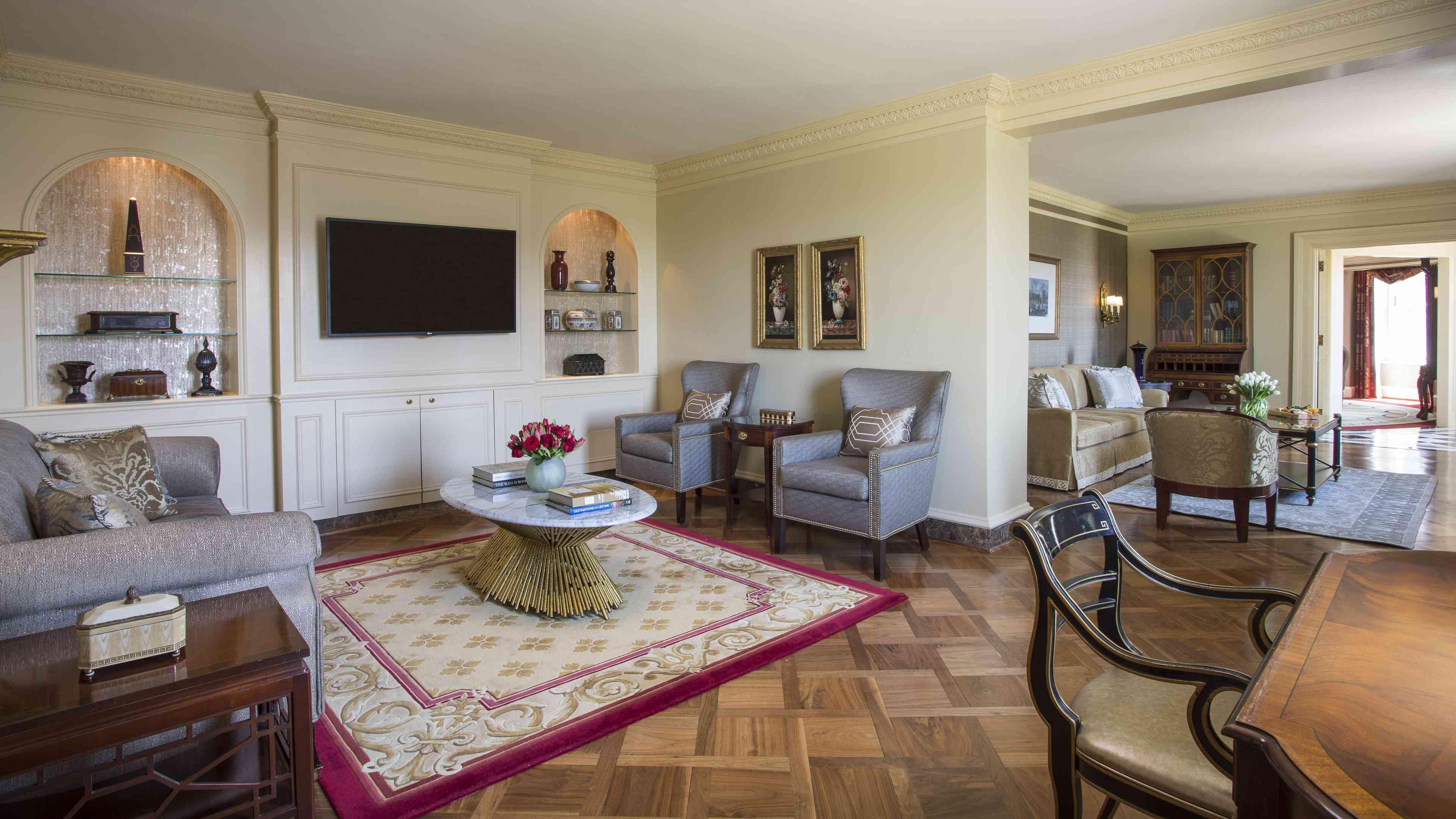 Sala de estar de la suite presidencial Thomas Jefferson en el Willard Intercontential. Hay un sofá gris para dos personas frente a dos sillones grises con una alfombra roja y crema que los separa