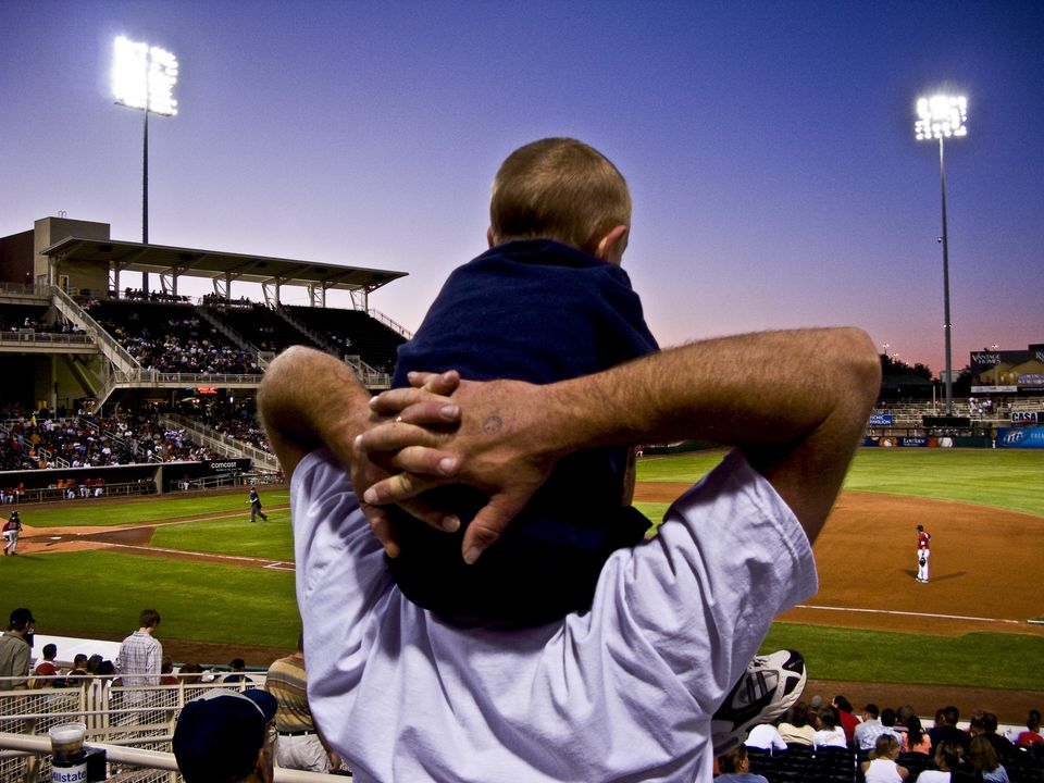 Father with son on shoulders at an Isotopes baseball game.