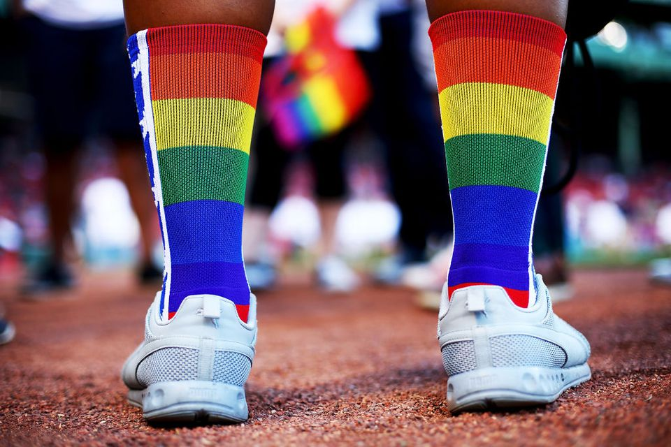 person's legs wearing white sneakers and calf-high rainbow striped socks
