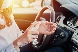 Woman in car putting on hand sanitizer