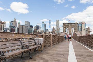 People walking down the brooklyn bridge with the manhattan skyline behind them