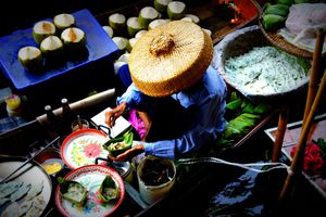 Woman preparing food in a boat at the floating market in Thailand