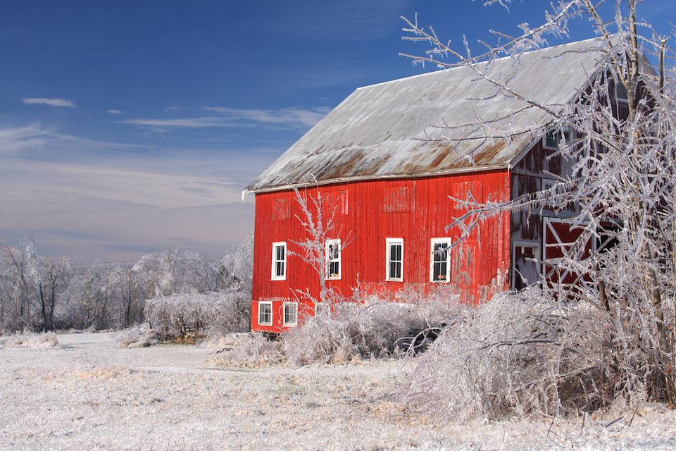 A red barn sits in a snowy field.