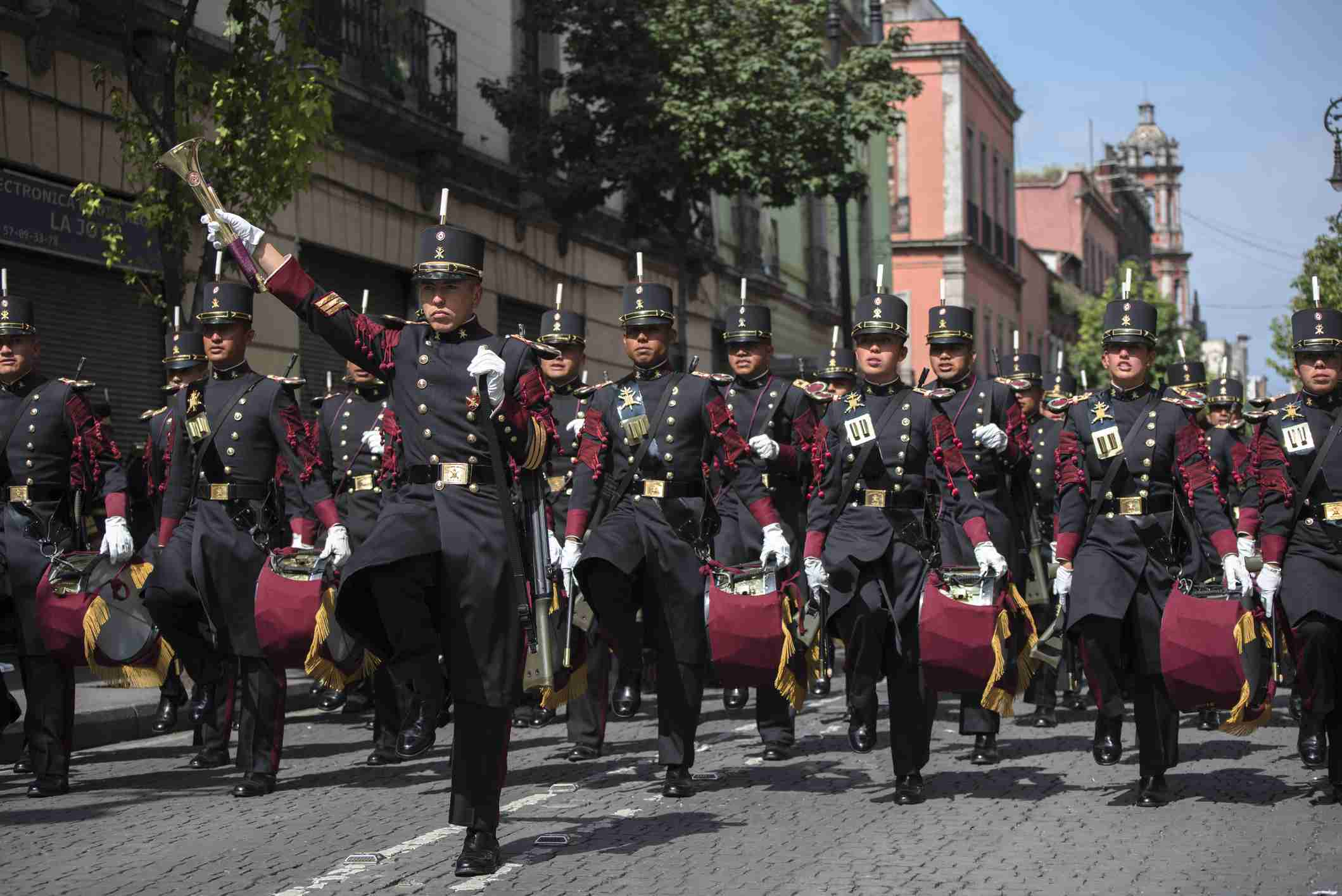 Military personnel dressed in balck and red uniforms and carrying drums in the Mexican independence day celebration