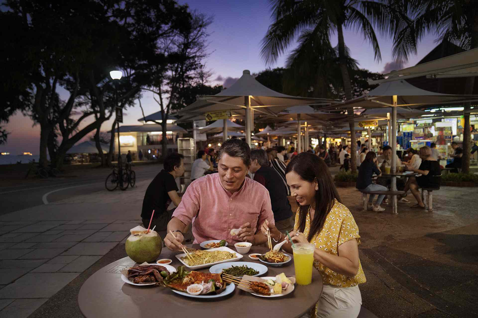 Couple eating at open-air hawker center, Singapore