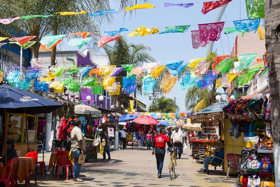 People shopping in Tijuana below colorful flags