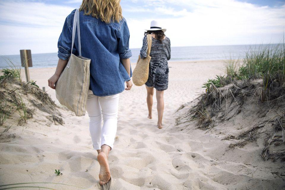 Women walking on sandy beach, Amagansett, New York, USA