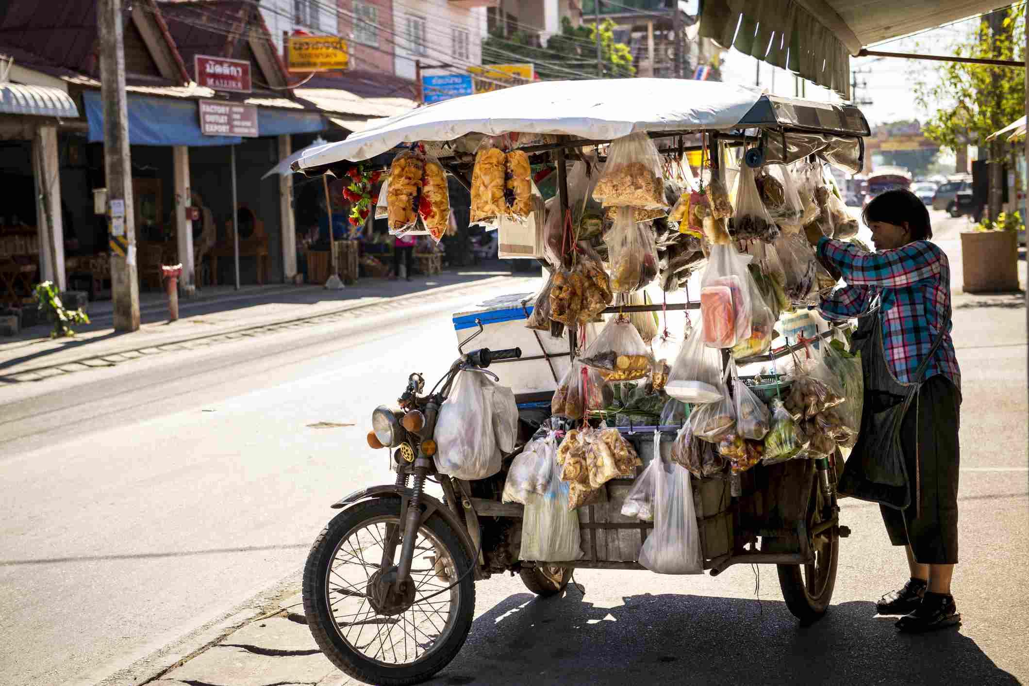 Thai woman selling snacks from motorbike cart