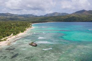 White sandy beach on a tropical island and clear sea. Top View of paradise tropical beach in sunny day. Coral reef Aerial view. Uninhabited island