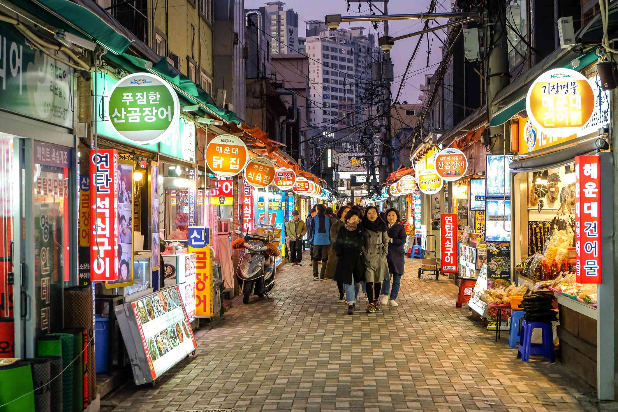 Tourist walking at haeaundae traditional market street with various shops and seafood restaurants