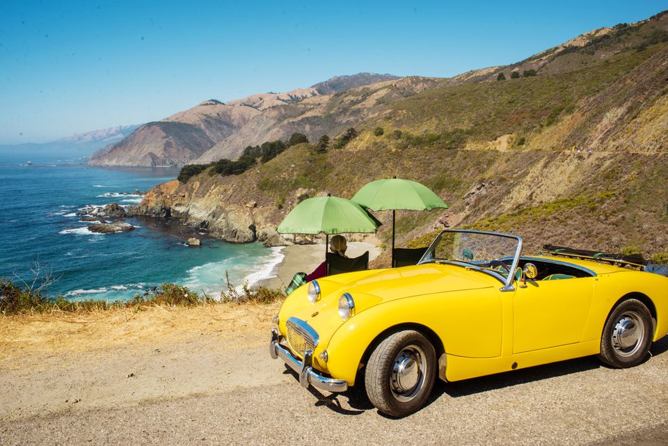 A classic Yellow car parked along Highway 1 with the passengers looking out over the cliffs of Big Sur