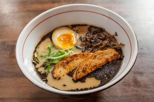 Bowl of shio ramen with half a soft boiled eggs, scallions, chicen, and soybean peast