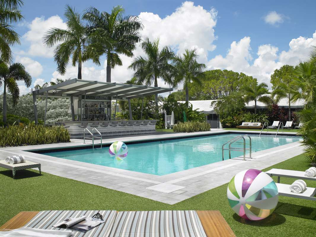 Hotel pool with a beach ball in the water and a beach ball on the grassy deck with a gray and white bar on one side of the pool