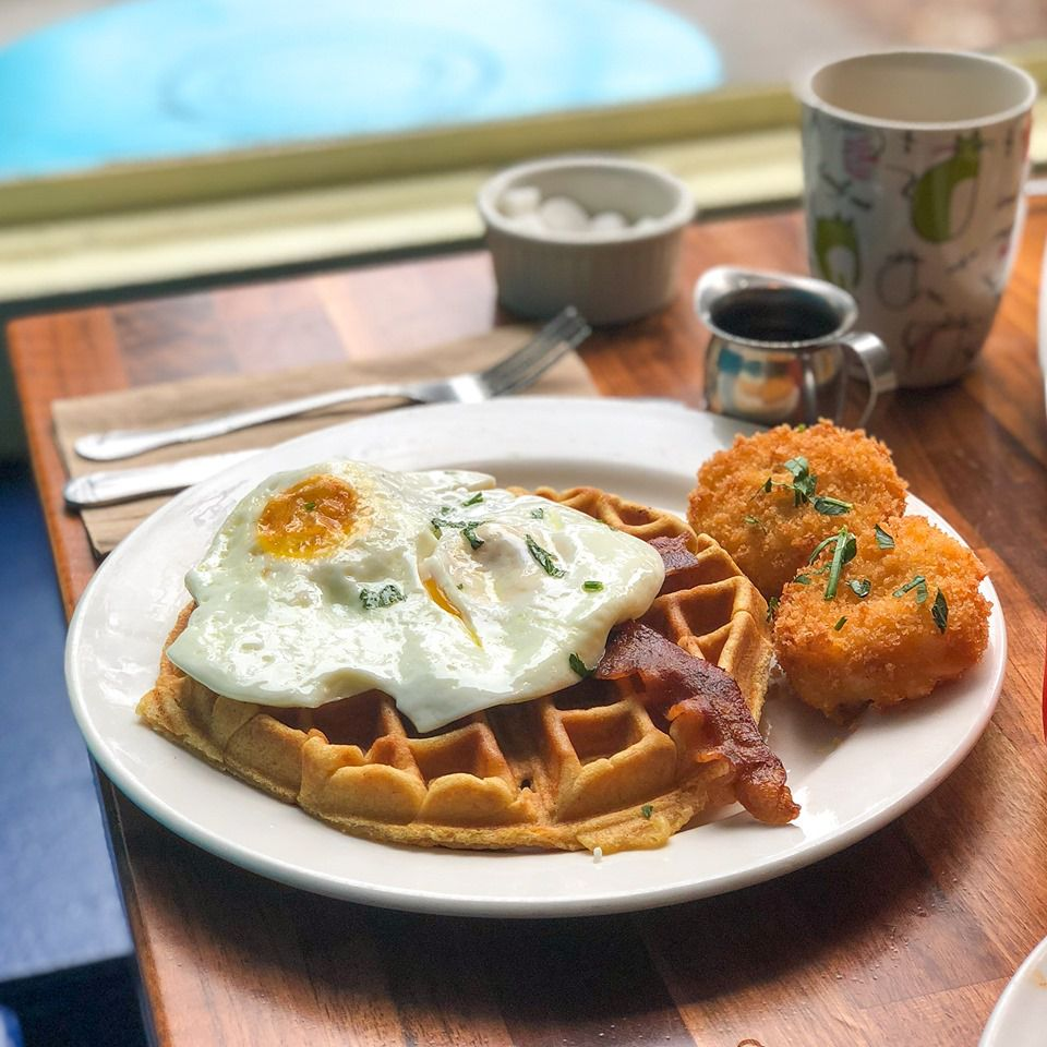 Wooden table with a coffe cup, syrup carafe, sugar bowl and knife and fork. There is also a plate with a waffle, with a piece of bacon and a fried egg on top, and two mashed potato croquettes