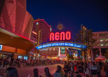 People lined up on the main street of Reno with the Reno sign lit up at night