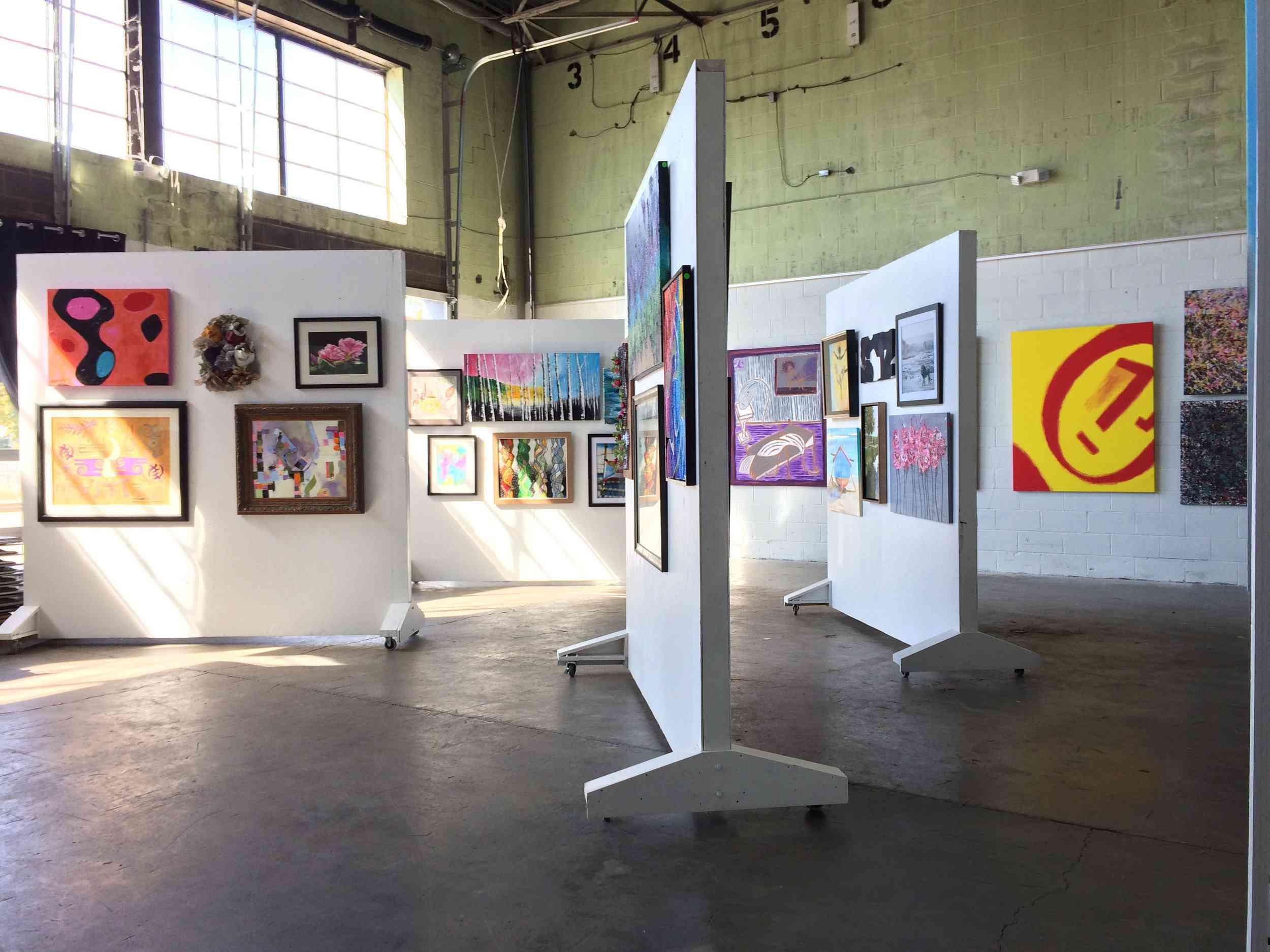 Varias paredes blancas móviles con obras de arte colgadas en ellas