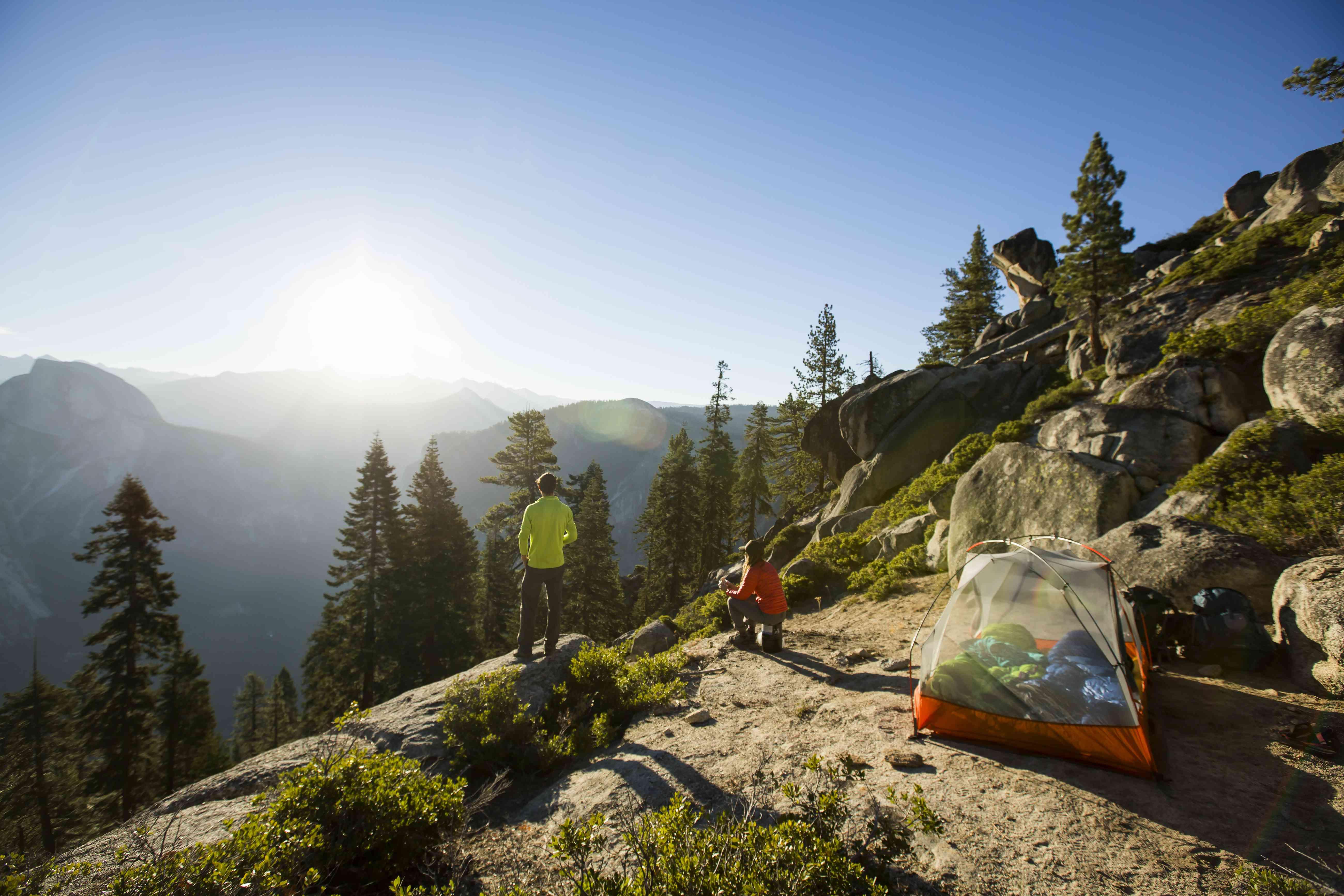 Una pareja mirando el amanecer mientras acampan