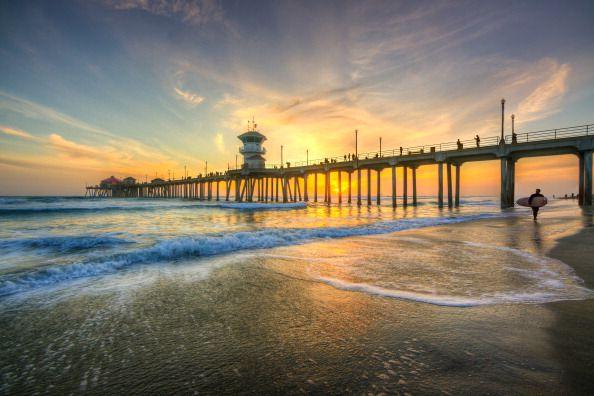 surfista caminando en Huntington Beach al atardecer con el muelle en el fondo