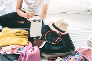 Midsection Of Woman Packing Luggage While Sitting On Bed At Home