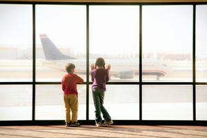 Boy and girl watching airplane at airport