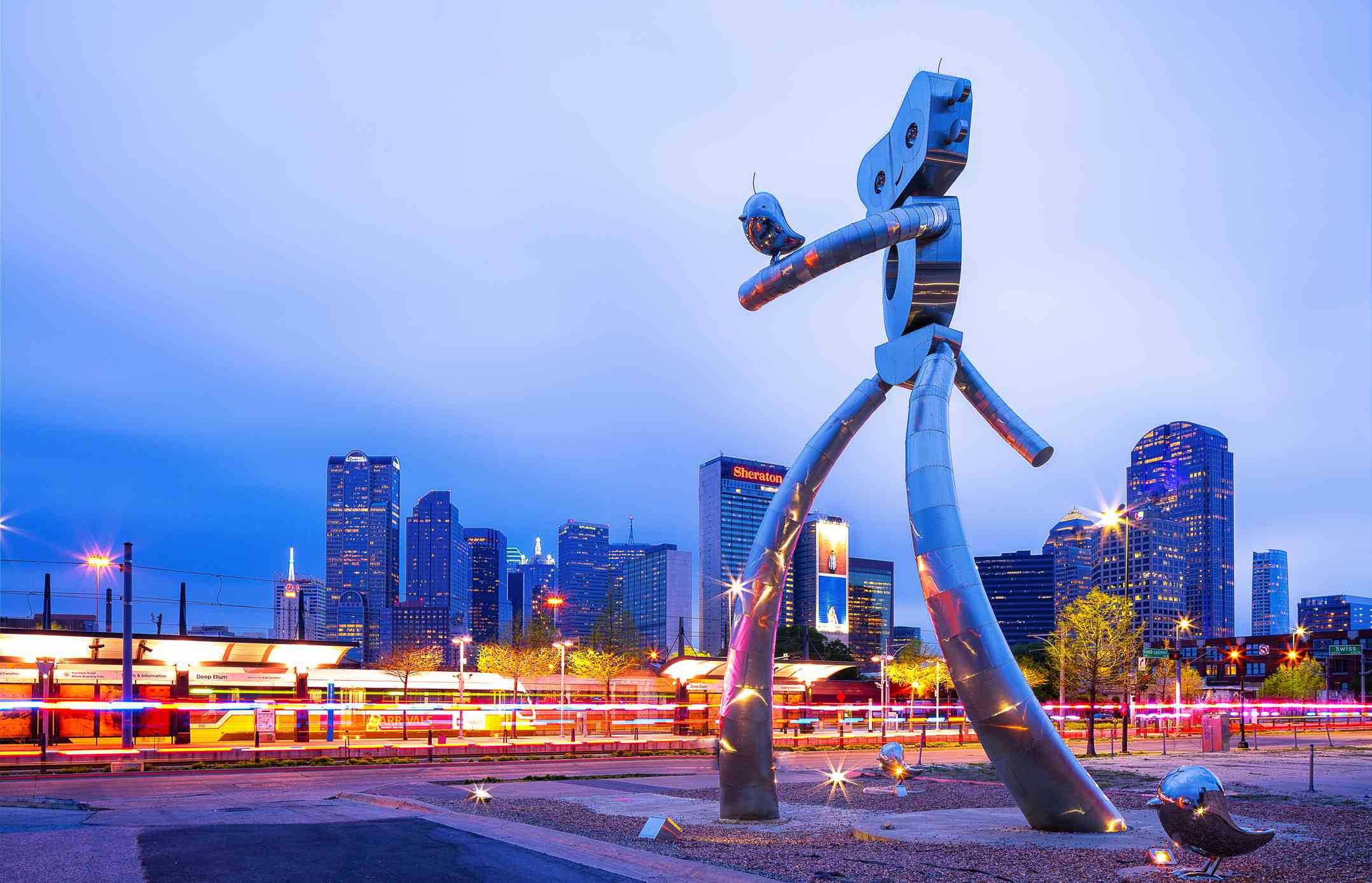 Large metal sculpture . of a robot with a bird on its arm at twilight in Dallas