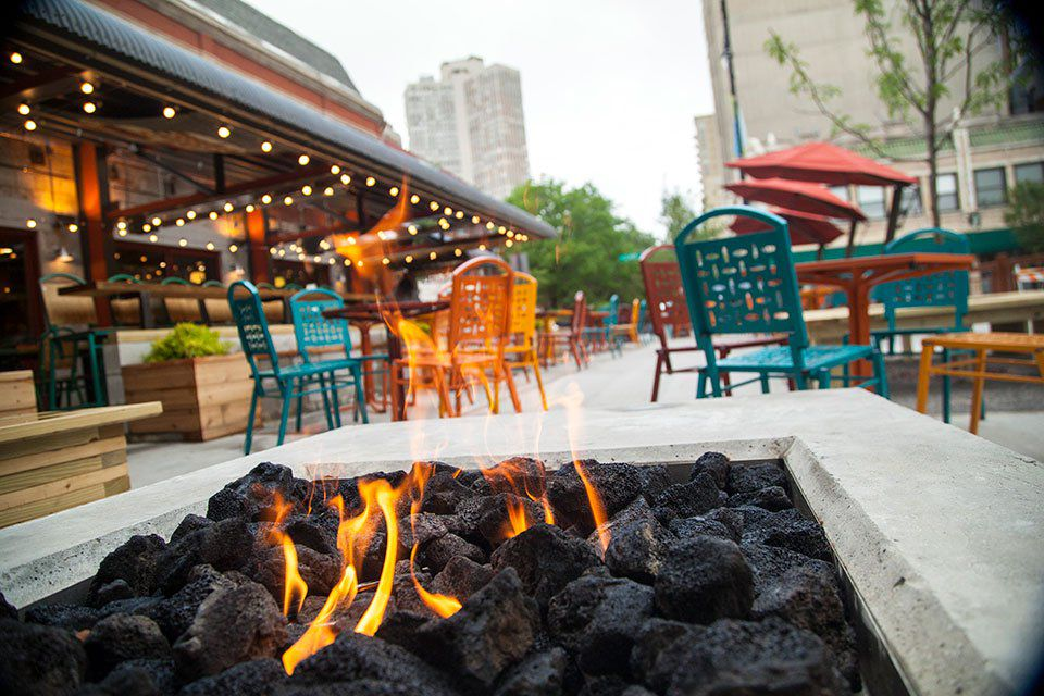 close up of a coal fire pit on a patio with colorful chairs
