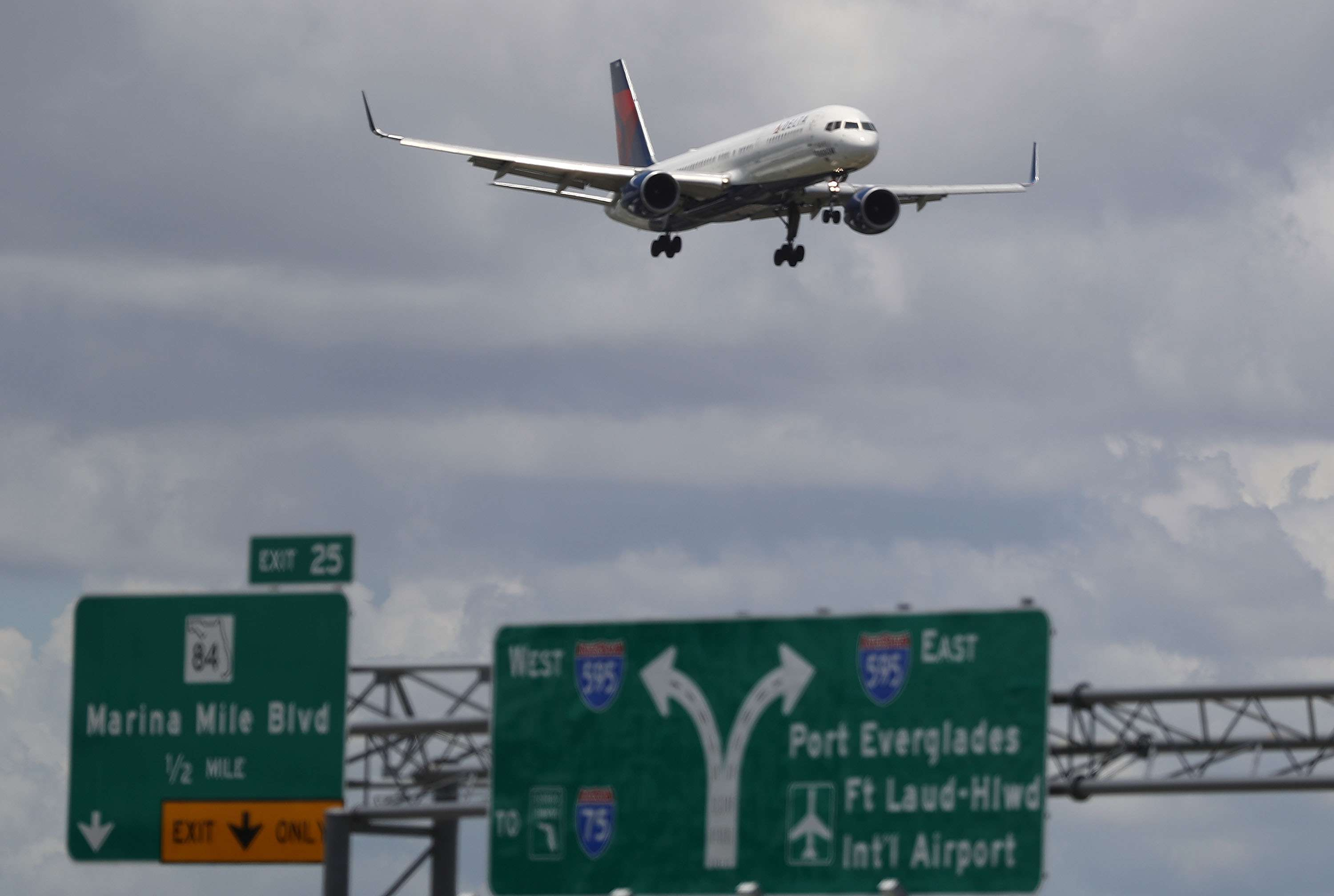 A Delta plane comes in for a landing with freeway signs for Ft Lauderdale Hollywood Airport visible