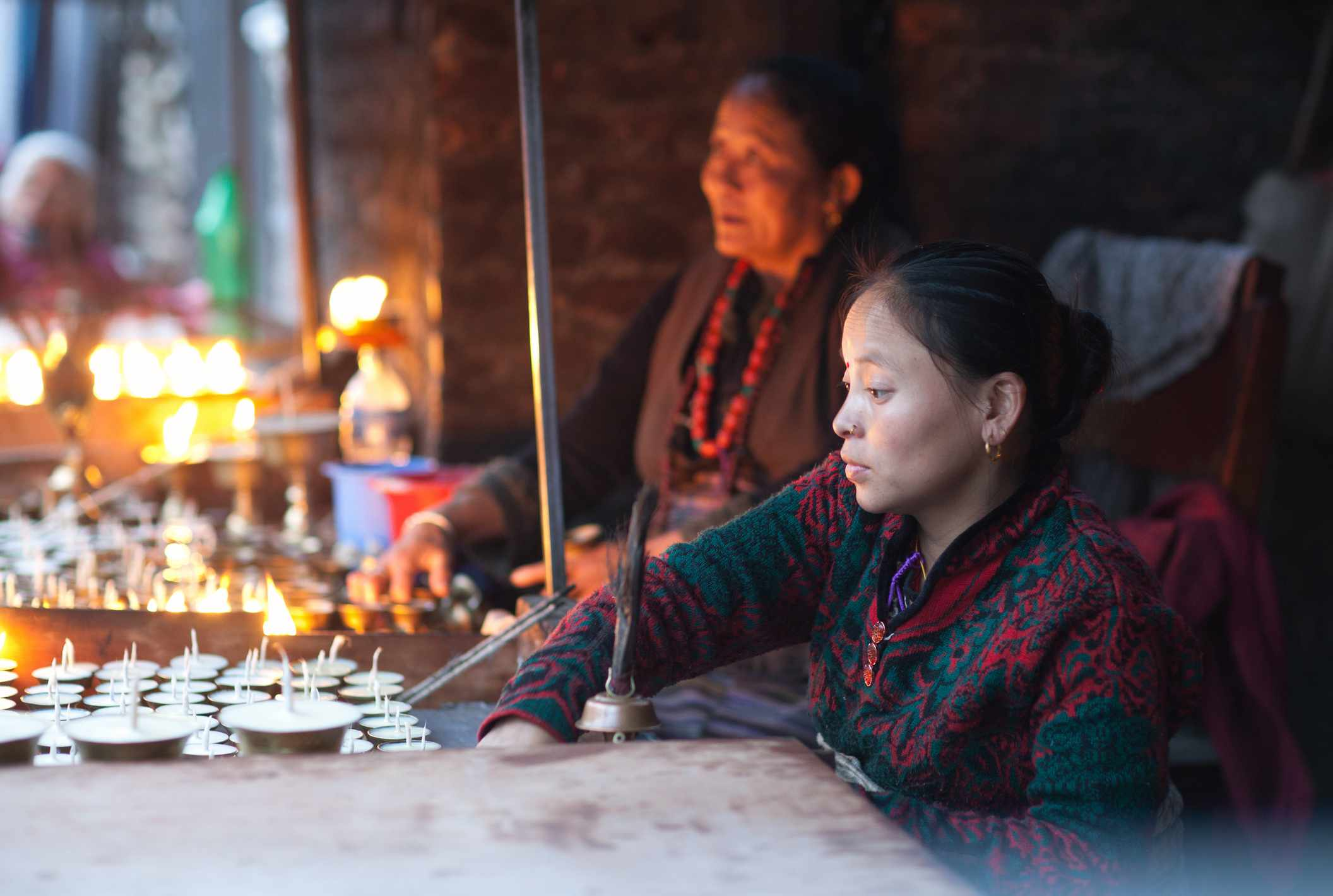 woman lighting butter lamps in a temple