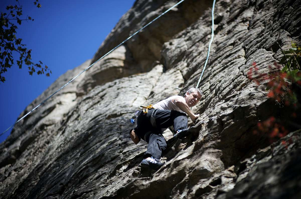 A rock climber descends a wall with a rope holding him firmly in place.
