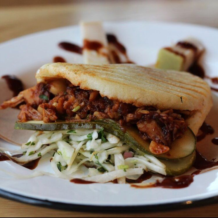 Arepa stuffed with barbecue jackfruit, pickle slices and pickled cabbagr