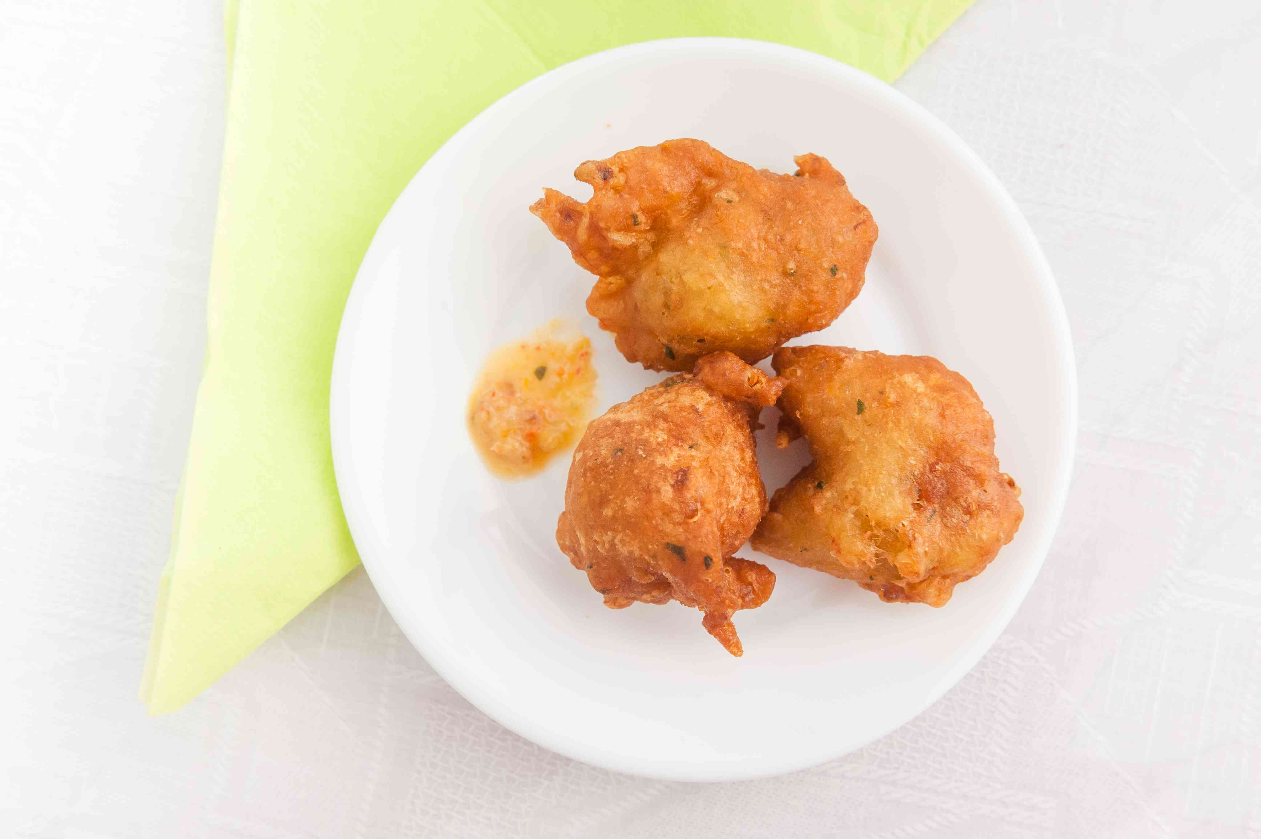 Three cod fritters on a white plate