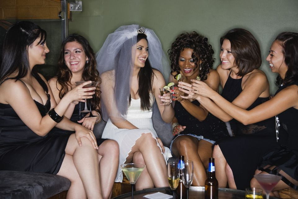 Friends drinking cocktails with bride in nightclub
