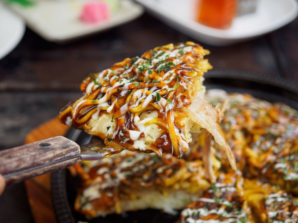 spatula holding a piece of okonomiyaki over a pan of the dish