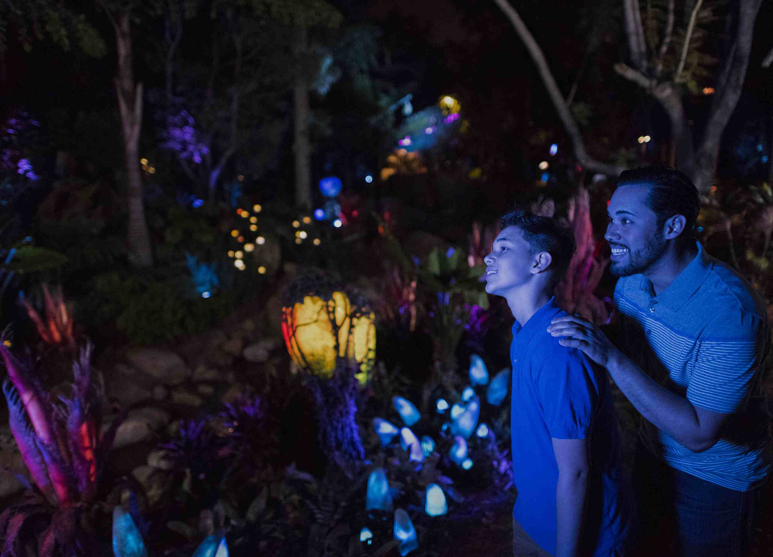 Father and son smiling at the Bioluminescent Plants at Pandora World of Avatar