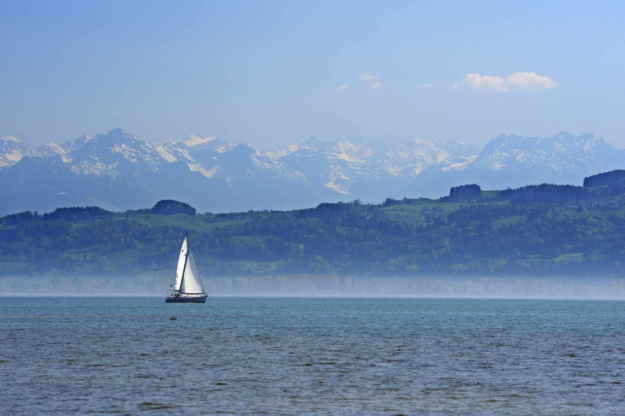 Velero con los Alpes suizos en el fondo, el lago de Constanza, Wasserburg, Lindau, Baviera, Alemania