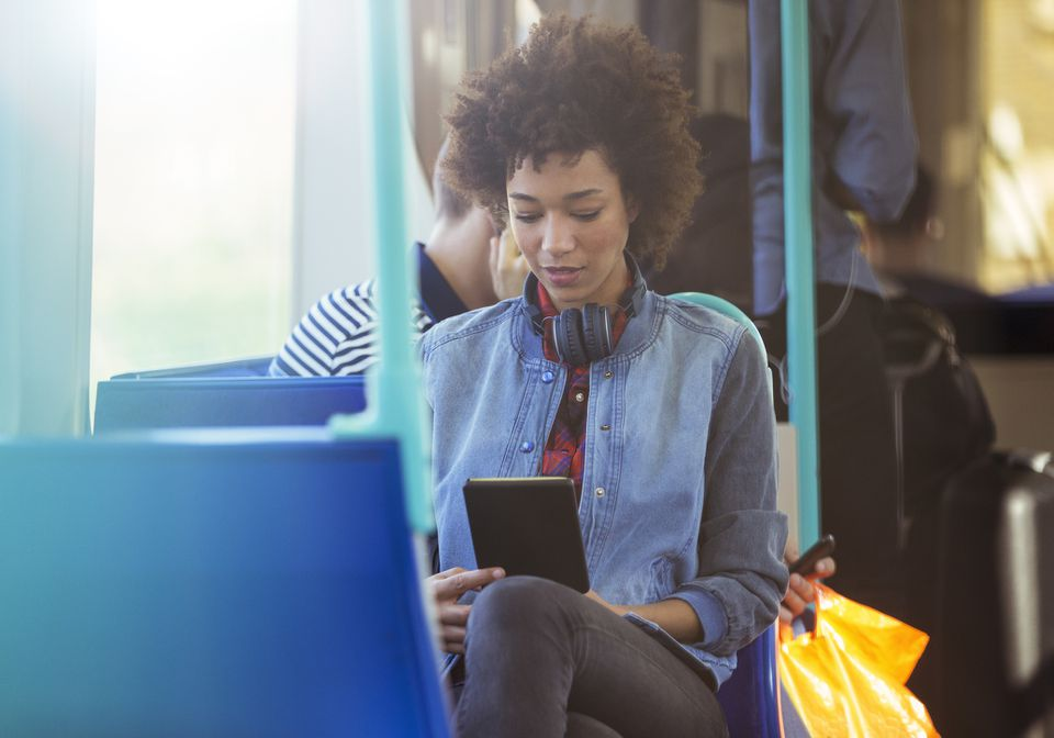 Woman with her Kindle on the bus