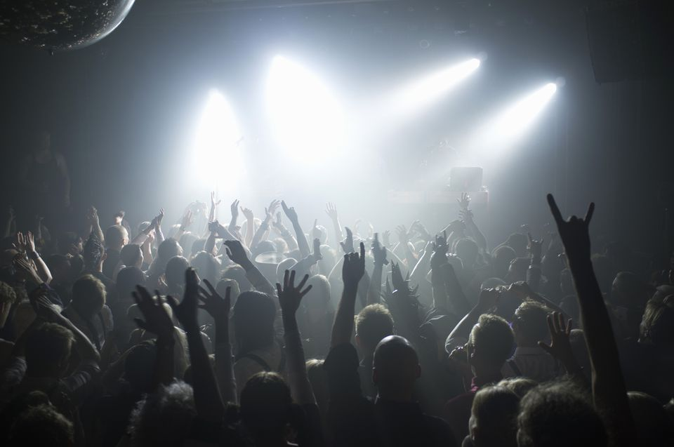 Rays of white spotlights over crowded dance floor at nightclub