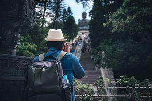 Tourist taking picture of Tian Tan Buddha in Hong Kong