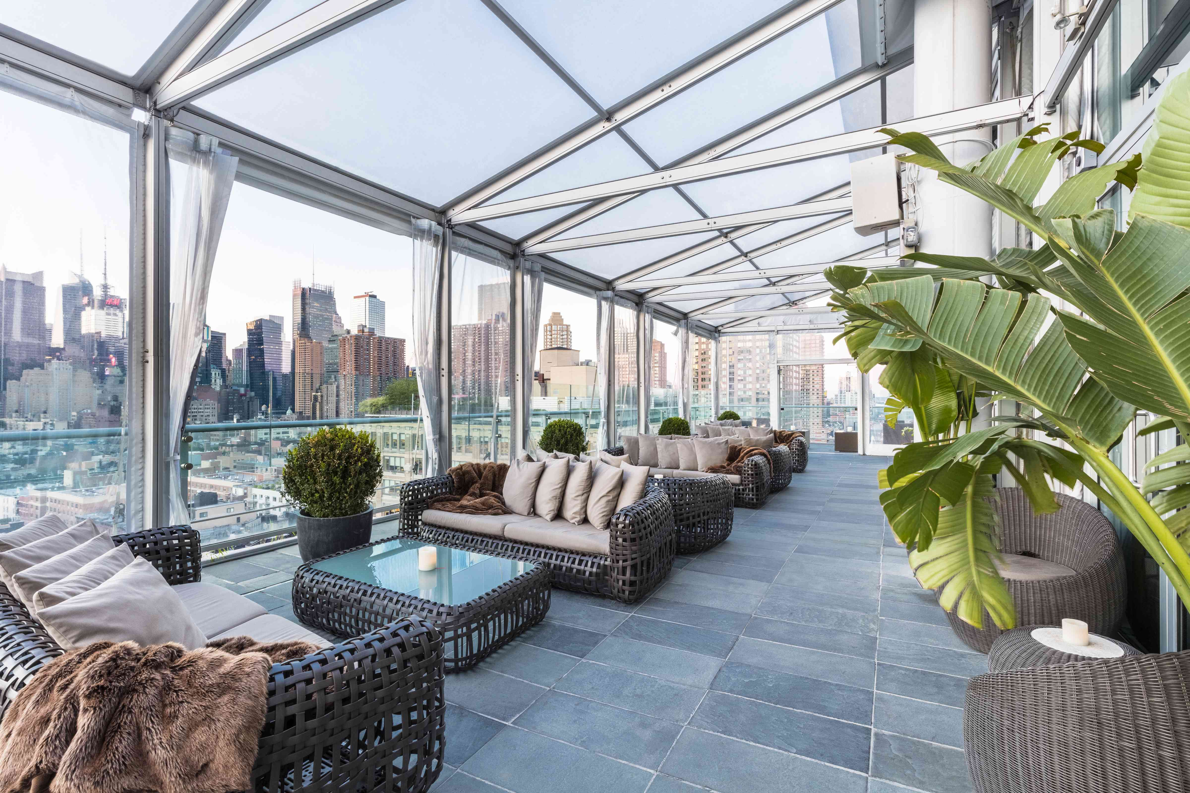 Glass enclosure with a series of faux-wicker couches a a few potted plants