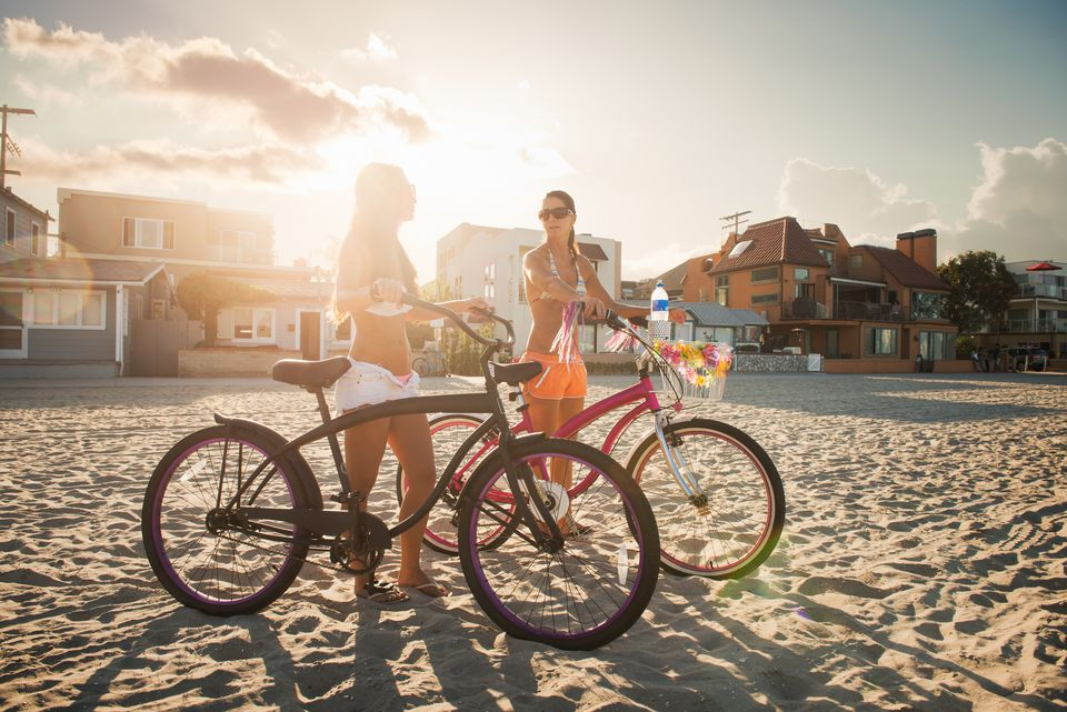 Two women cyclists chatting on beach, Mission Bay, San Diego, California, USA