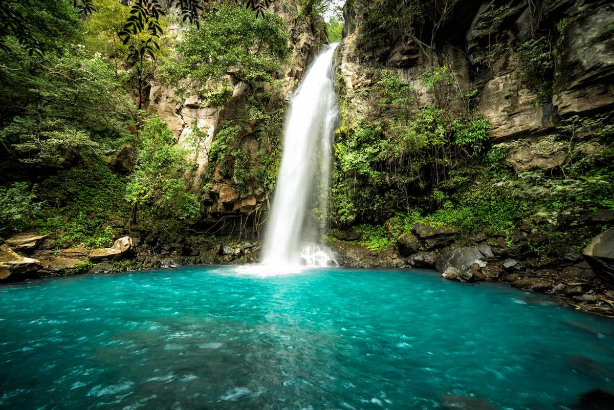 Blue lake with a waterfall in Rincon de la Vieja National Park