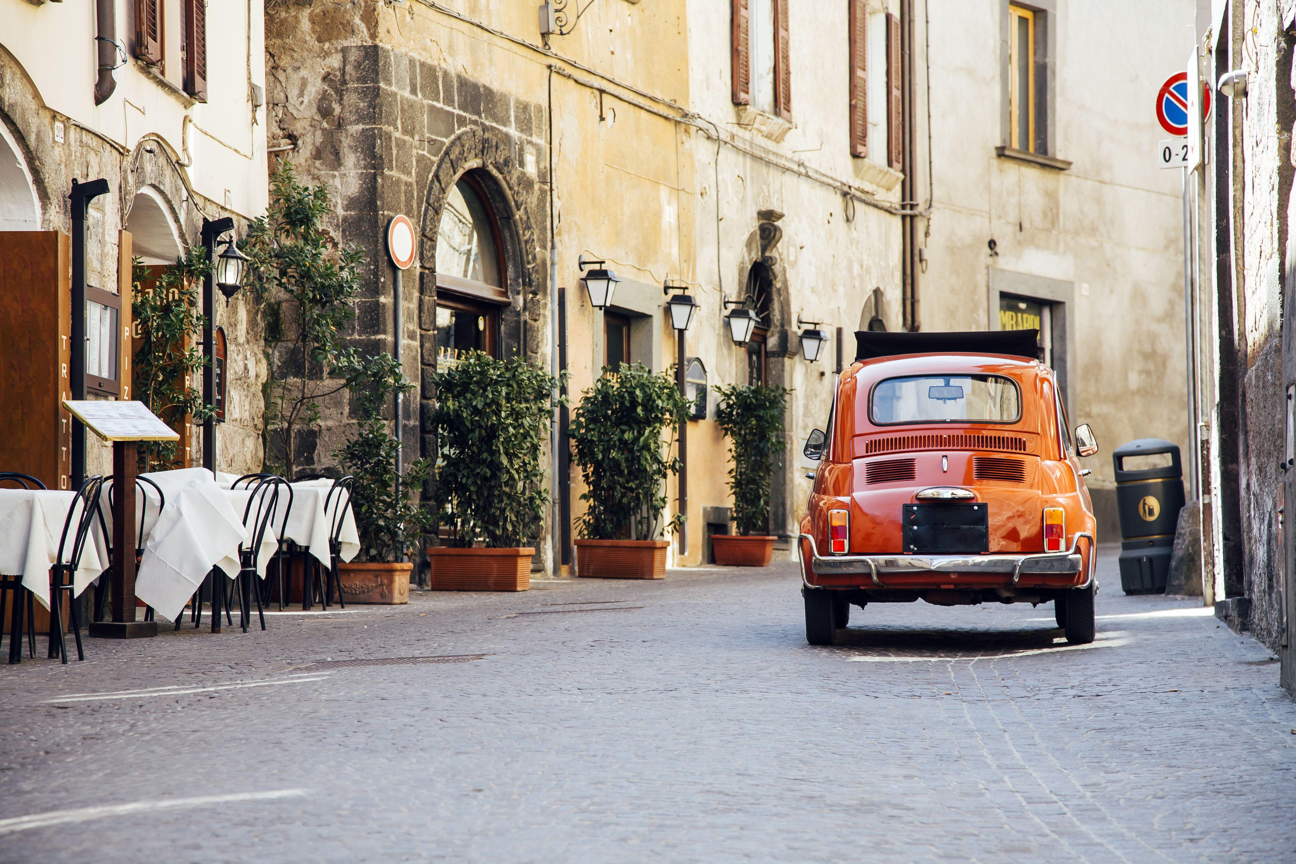 Viejo auto clásico rojo en la calle angosta de Italia