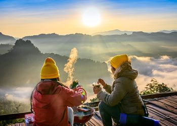 two people in yellow beanies enjoying a hot drink while looking out at mountains and fog below