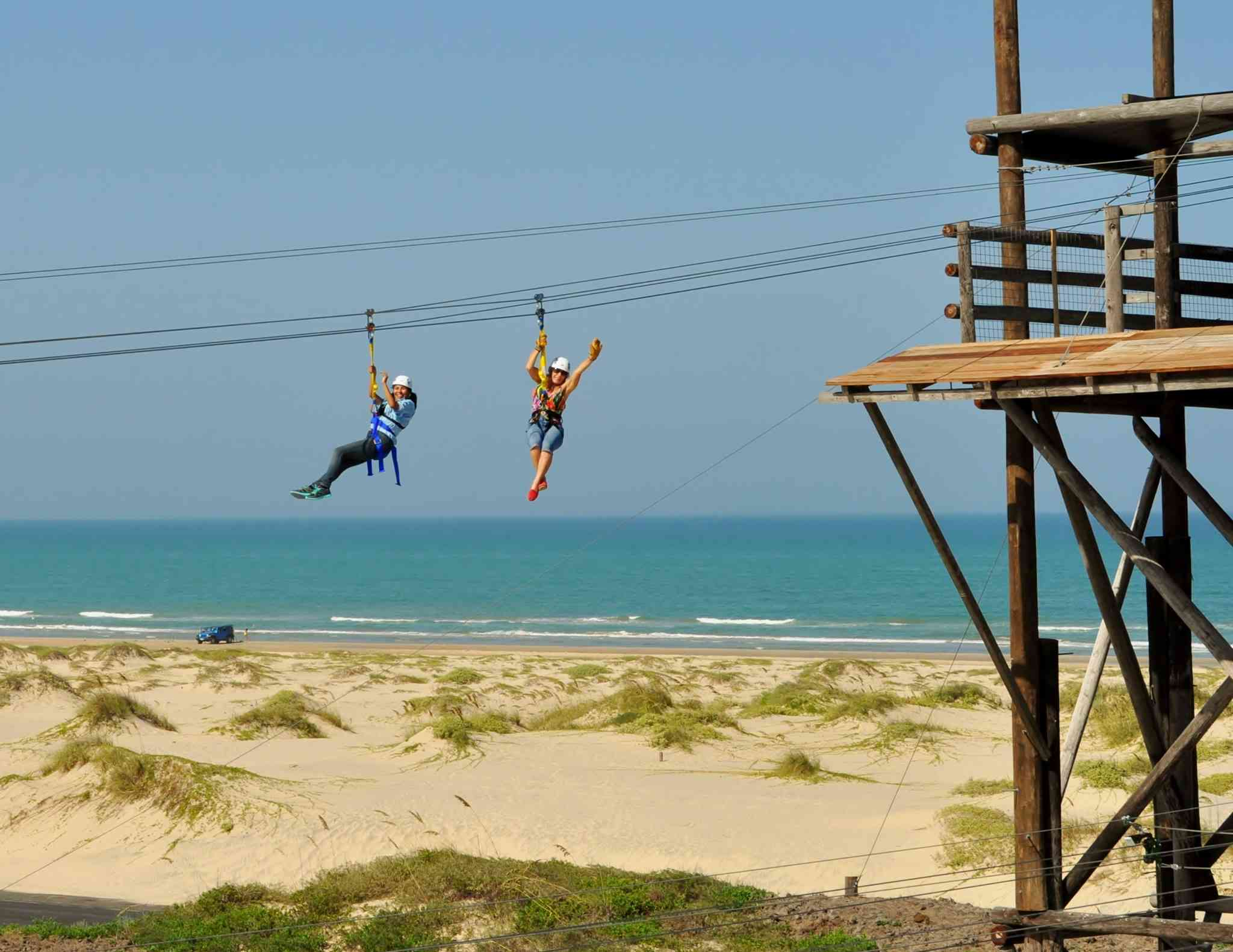 Two people zipline above the sand and sea