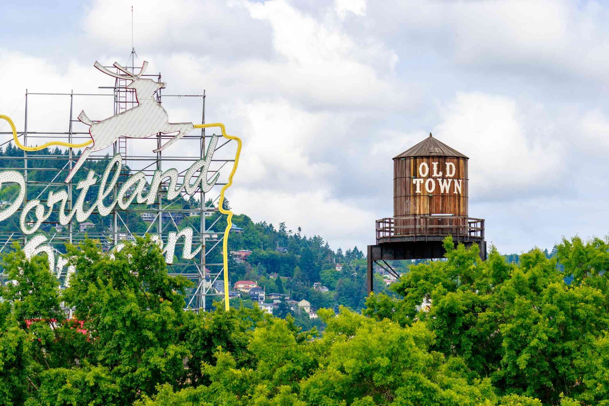 The White Stag sign, a former advertising sign, in Old Town, Portland partial covered by trees close to a wooden water tower that says