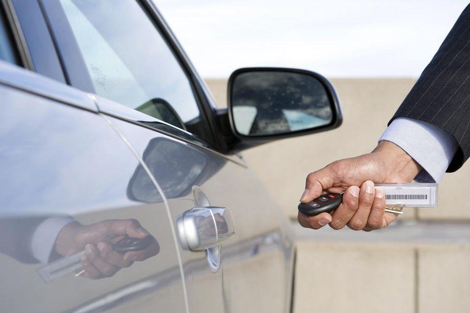 Hispanic businessman using electronic key to open car door