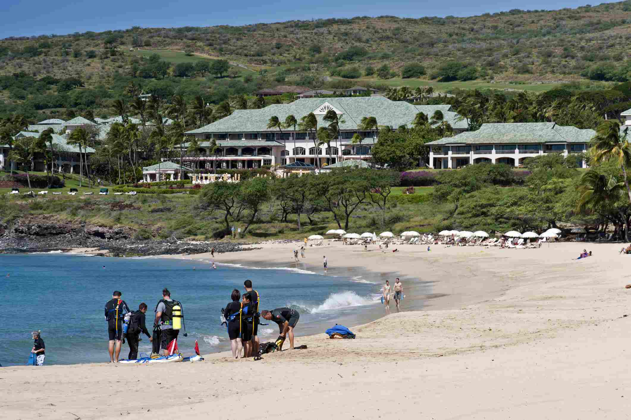 Couples, families, and friends enjoy a day at the beach adjacent to the Manele Bay Hotel on the Island of Lanai