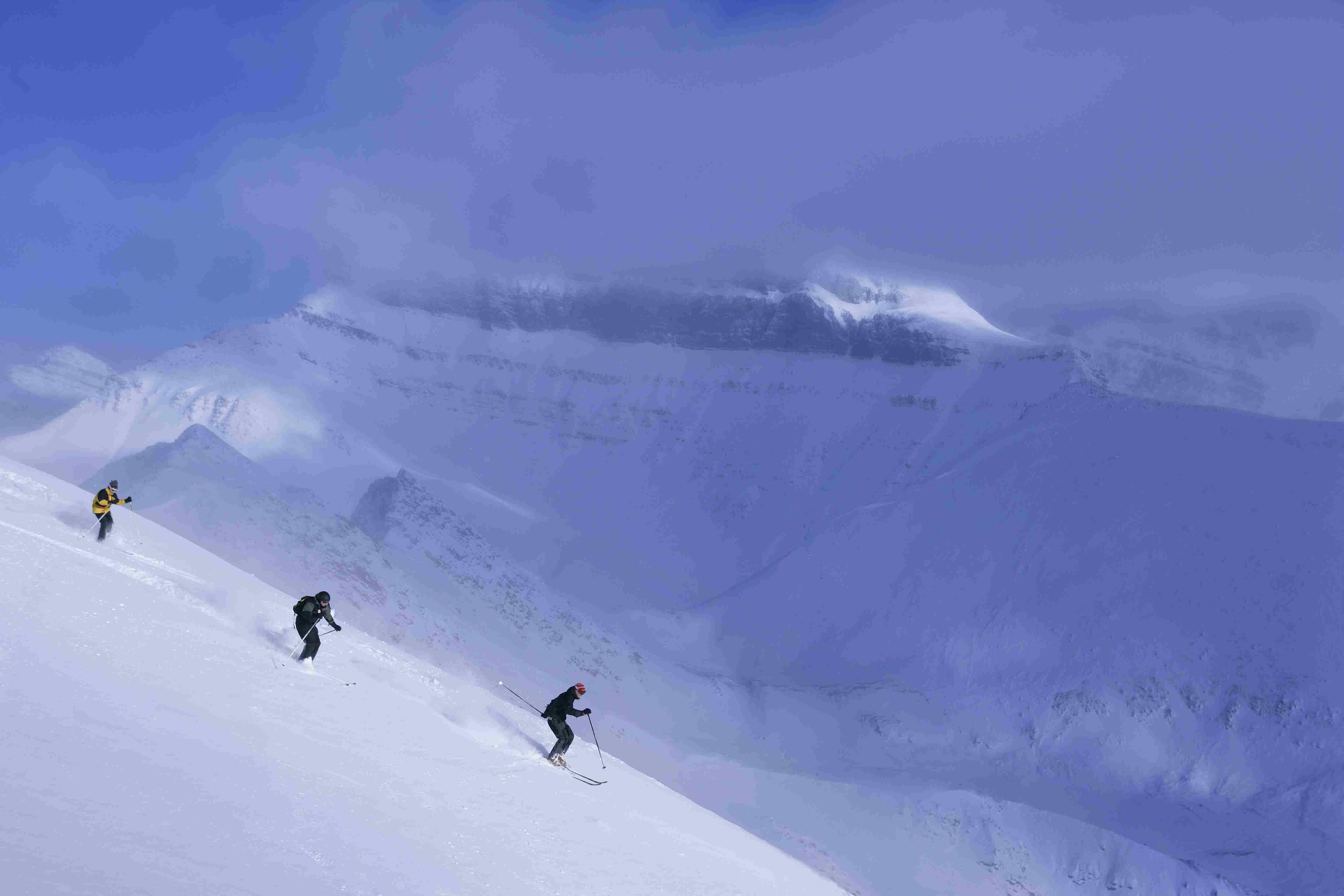Three skiers in deep snow, Lake Louise, Alberta, Canada